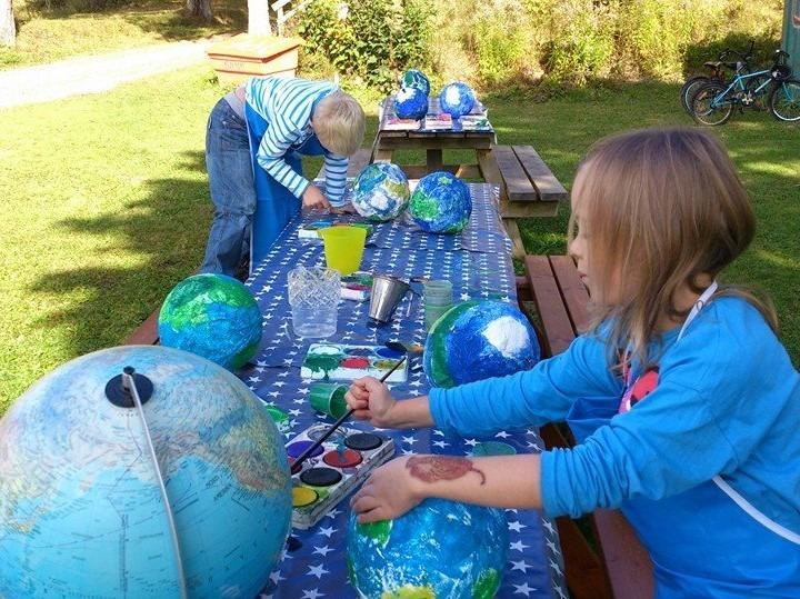 Barn som målar jordglobar av papier mache