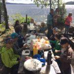 Skolbarn fikar utomhus vid sjön