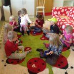 Flera barn som sitter i en cirkel på golvet och äter frukt