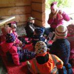 Flera barn samlade i vindskydd utomhus