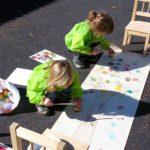 Barn som ritar ett stort träd på ett lång papper