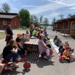 barn sittandes utomhus där alla ser åt ett håll