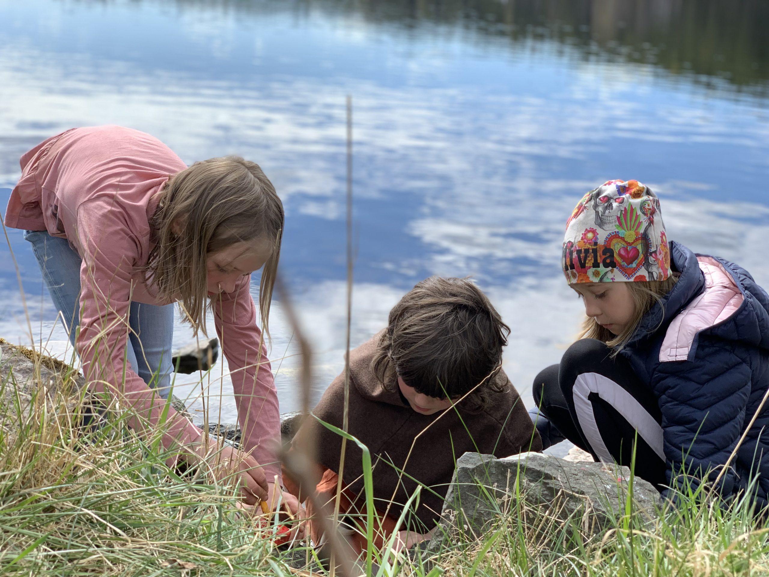 tre barn med sjö i bakgrunden