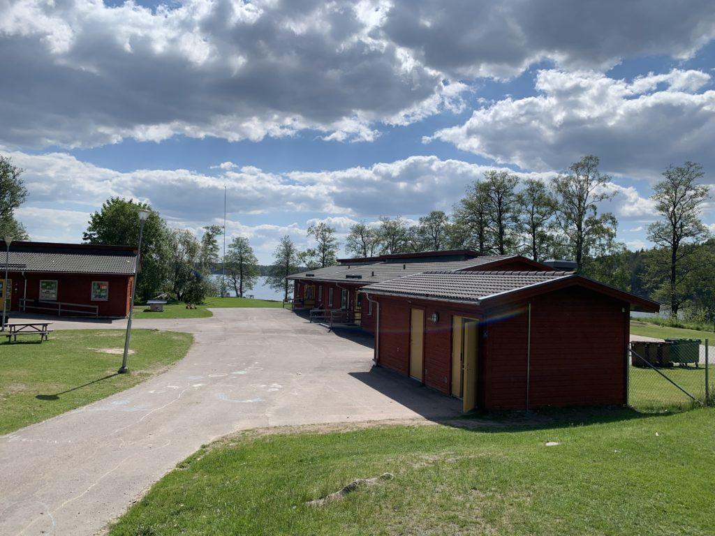 skolbyggnad röd med gräsområde kring