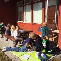 Barn läser och ritar uthomhus