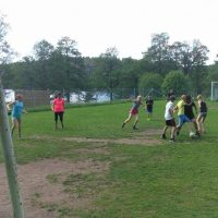 Barn och lärare som spelar fotboll