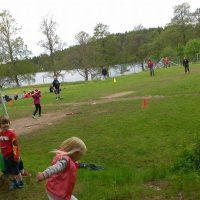 barn och vuxna som är utomhus på en stor plan och spelar brännboll
