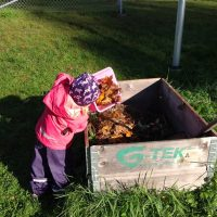 Barn vid en kompost
