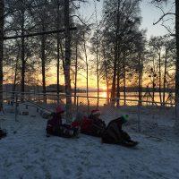 Barn som åker pulka med sjön Yngen i bakgrunden och solnedgång